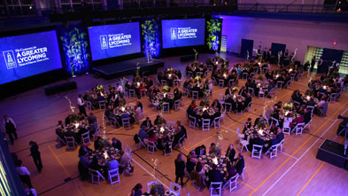 An elevated view of the tables, stage, and screens at the gala event